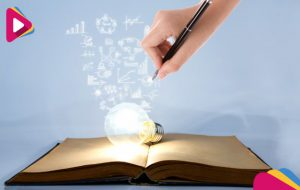 person drawing symbols coming out of a light bulb on top of a book 1232 909